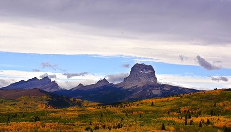 A wide view of the iconic Chief Mountain encompasses its surrounding peaks, a foreground of Fall colors as well as a sky mixed with dark clouds, white puffy clouds and a streak of bright blue. Stock Photo