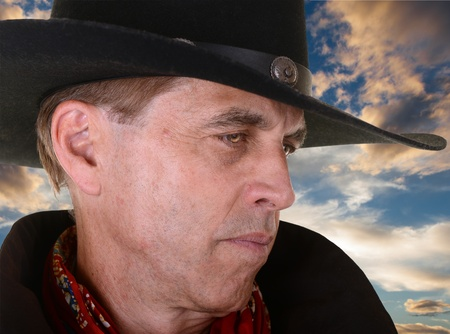 profile of handsome serious man wearing a black cowboy hat and red bandana against beautiful sunset photo