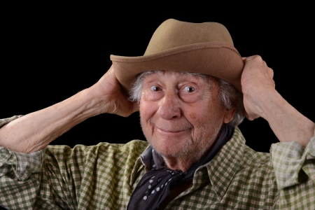 happy old man: funny old man wearing a green checked shirt and a tan felt hat
