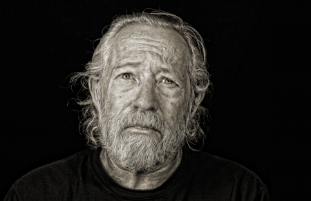 contemplation: Stressed out older man isolated against black sepia toned Stock Photo