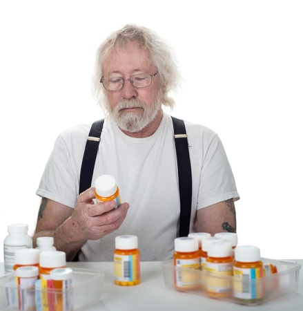 Senior looking at a bottle of pills with more bottles of pills on a table isolated on white photo