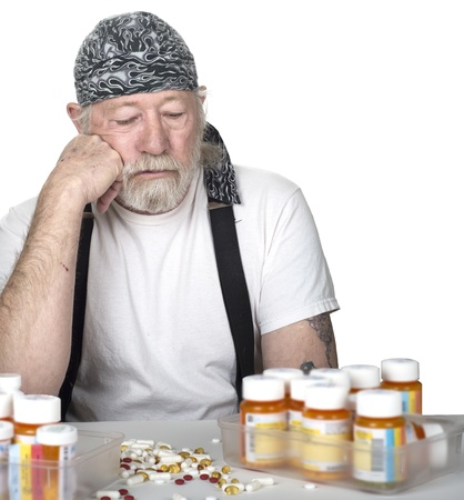 Tough old man in a white t-shirt and a bandana sitting in front of a table full of prescription bottles and pills isolated on white photo