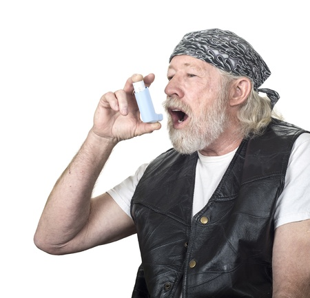 inhaler: Strong mature man using an inhalor isolated on white Stock Photo