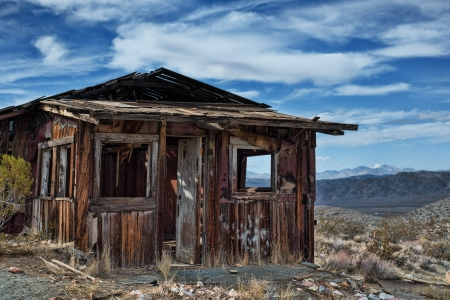western usa: Decayed cabin on hill in Randsberg California with beautiful cloudy sky and mountains in the back ground Stock Photo