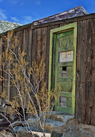 Green door on abandoned cabin in a ghost town photo