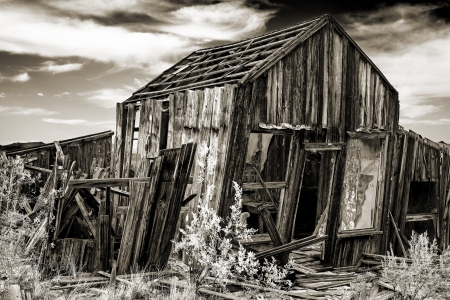 sepia toning: Monochrome with sepia toning of decayed leaning cabin with cloudy sky in Randsberg California Stock Photo