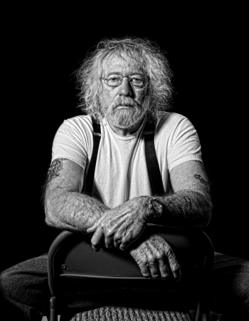Serious tough old man with wild hair in monochrome isolated on black photo
