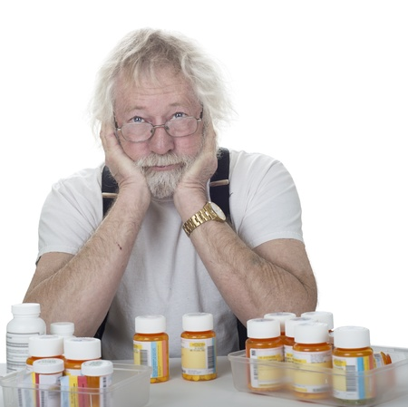 senior wearing glasses with a lot of prescription bottles of pills isolated on white Stok Fotoğraf