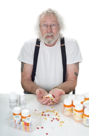 Senior with surpised look on face holding a handful of pills with prescription bottles on table isolated on white photo