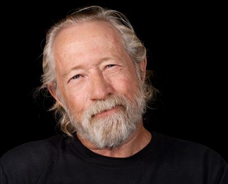 caras emociones: Viejo hombre con una mirada divertida en su cara aislados sobre un fondo negro terreno