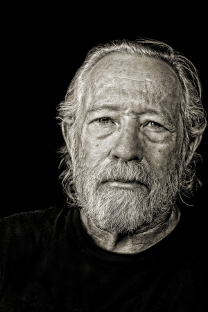 Toned black and white image of serious tough old man photo