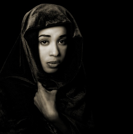 Serene African American woman wearing a shawl in monochrome with sepia toning isolated on black photo