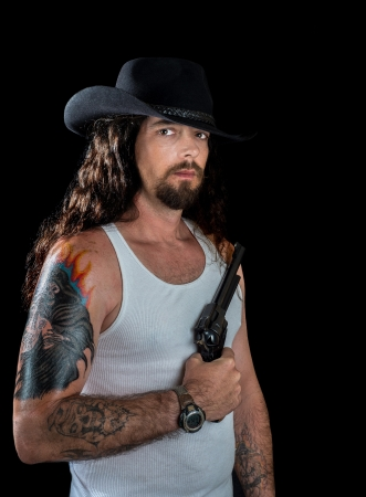 very handsome sexy man with long wavy brown hair and striking eyes wearing a black cowboy hat holding a revolver photo