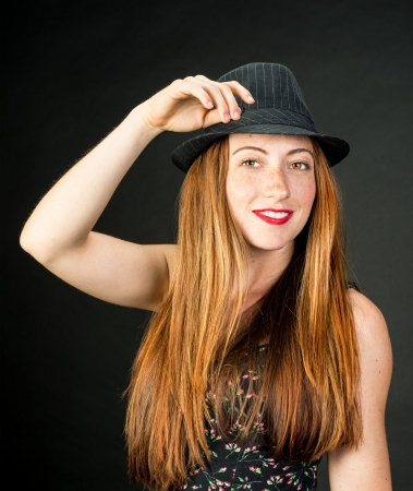 hazel eyes: Beautiful fresh young lady with lovely hazel eyes red hair and freckles wearing a pinstriped fedora against a gray background