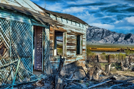 tourquoise: Abanonded tourquoise house in Mojave National Preserve with old picket fence train tracks and dramatic mountains in the background