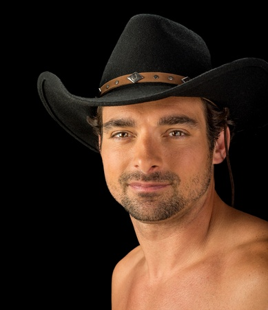 Very handsome sexy brown eyed man without a shirt wearing a black felt cowboy hat isolated on black  photo