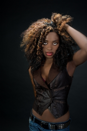 Sultry exotic African American woman with big hair and beautiful red lips against a dark background