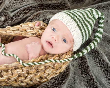 Adorable blue eyed newborn in a knit basket with a green and white knit cap on a fur blanket photo