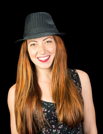 hazel eyes: Happy smiling young woman with long red hair and hazel eyes wearing a pinstriped fedora isoaled on black
