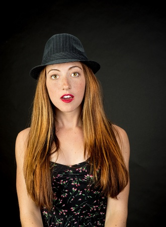 hazel eyes: Very cute girl with red hair freckles and beautiful hazel eyes wearing a pinstriped fedora against a dark background Stock Photo