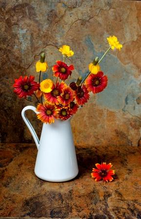 Beau bouquet de fleurs sauvages dans un pot blanc sur fond ardoise en couleurs d'automne