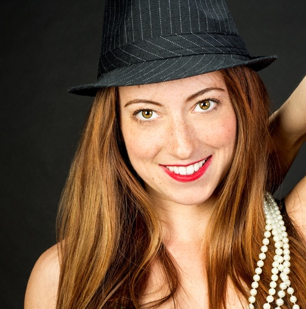 hazel eyes: Closeup of adorable red haired woman with beautiful hazel eyes Wearing a fedora smiling