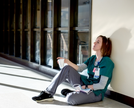 Exhausted nurse sitting on the floor with her eyes closed holding a cup Banque d'images