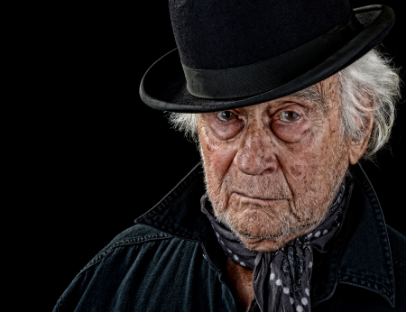 Vintage looking old man with a black coat, gray scarf and black bowler hat staring straight at the camera isolated on black