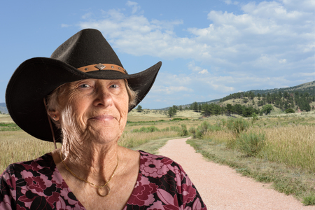 wino: Senior lady wearing a black cowboy hat a rural scene behind her