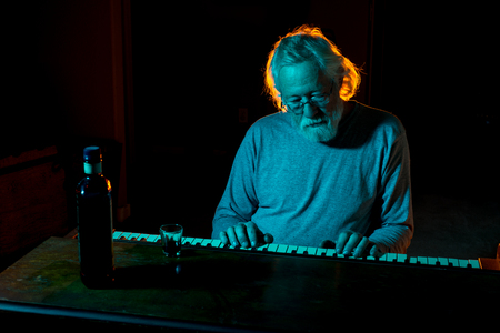 Senior man playing an old piano while drinking alcohol with dramatic lighting in blues and oranges photo