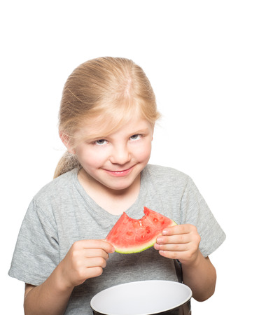 mischevious: Child with gray eyes and blond hair looking mischevious eating watermelon isolated on white