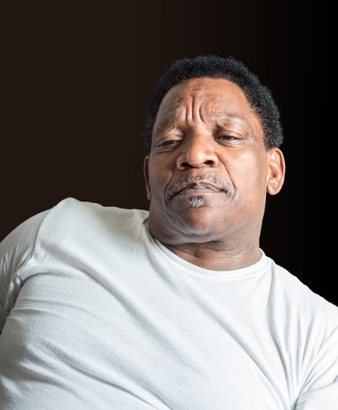 concerned African American man wearing a t-shirt against a dark background