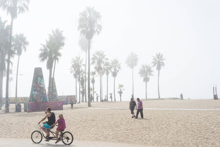 A couple riding a bicycle built for two and people walking in the sand on a misty morning