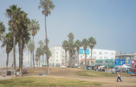 Shoppers walking along Venice Beach boardwalk and people sitting on the grass on a misty morning