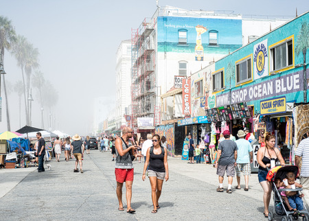 Shoppers walking along Venice Beach boardwalk on a misty morning with building construction in the background