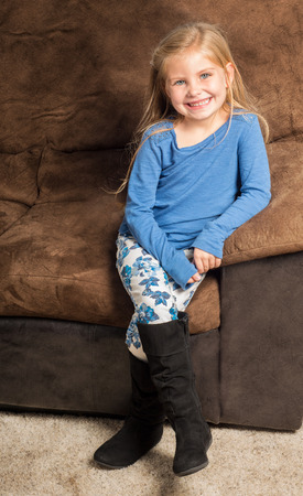big smile: Pretty little girl sitting on a brown sofa with a big smile wearing black boots