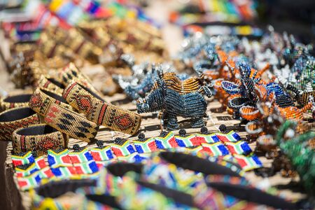 Colorful South African Bead Art in Bracelets, Rhino and Hippos in open air market Stok Fotoğraf