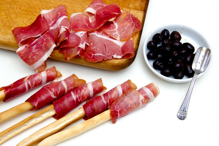 Slices of ham on cutting board and black olives on white background