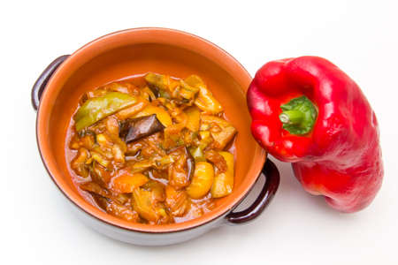 Sweet and sour peppers in the clay pot on white background photo