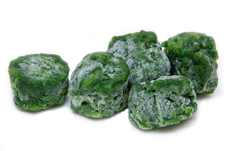 Cubes of frozen spinach on white background