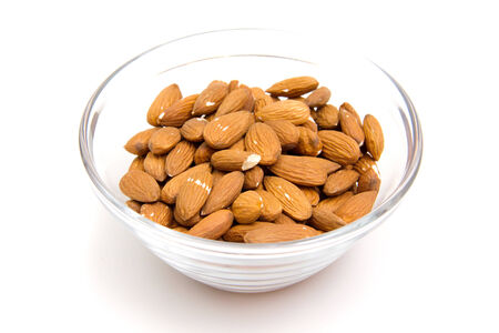 Almonds in a glass bowl on white background