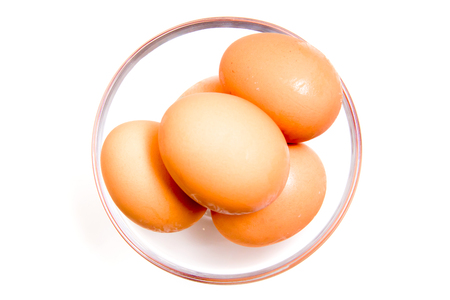 Eggs in glass bowl on white background from above photo
