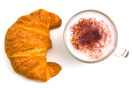 Cappuccino and croissant seen from above on white background