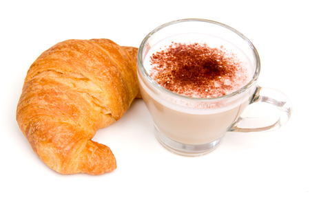 Cappuccino and croissant seen up close on a white background