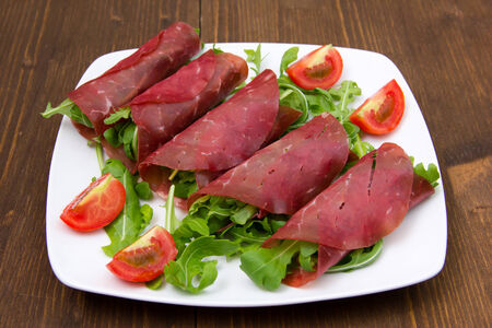 Rolls of dried beef on plate over wooden table
