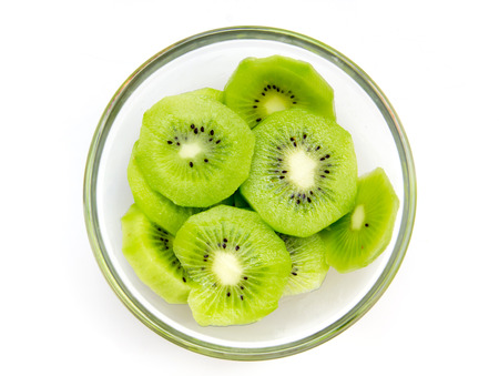 Slices of kiwi fruit on bowl on white background viewed from above Banque d'images