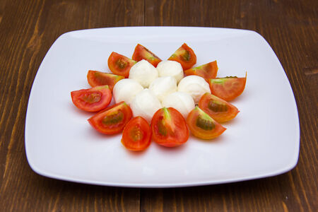 Plate with mozzarella and tomato on wooden table photo