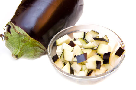 Cubes of eggplant on bowl on white background Banque d'images