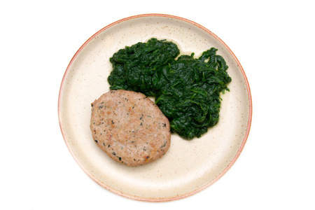 Hamburger meat with spinach on white background seen from above photo