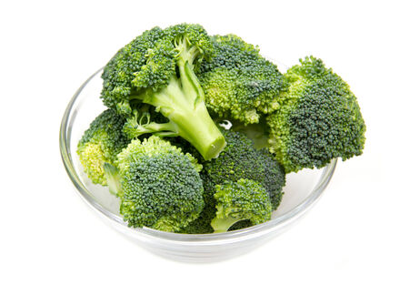 Broccoli in glass bowl on white background photo